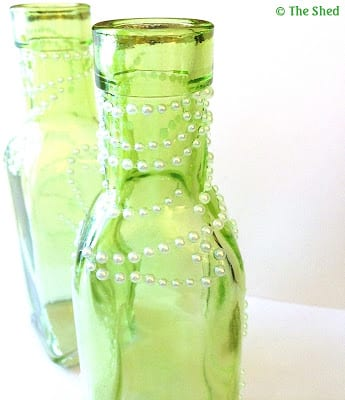 small green glass bottles embellished with tiny white pearls