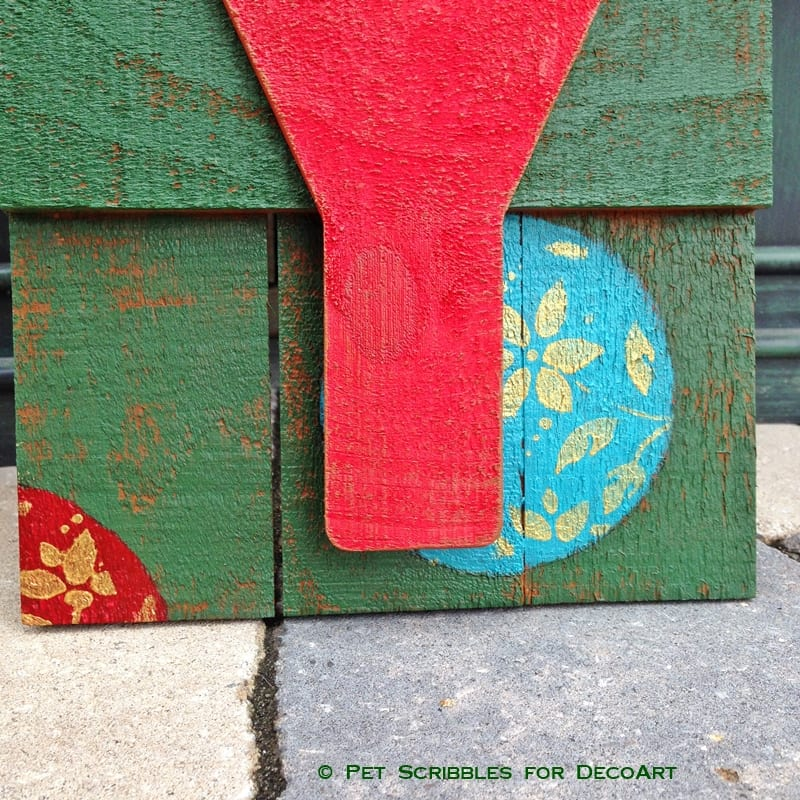 stenciled and painted ornaments on wood sign