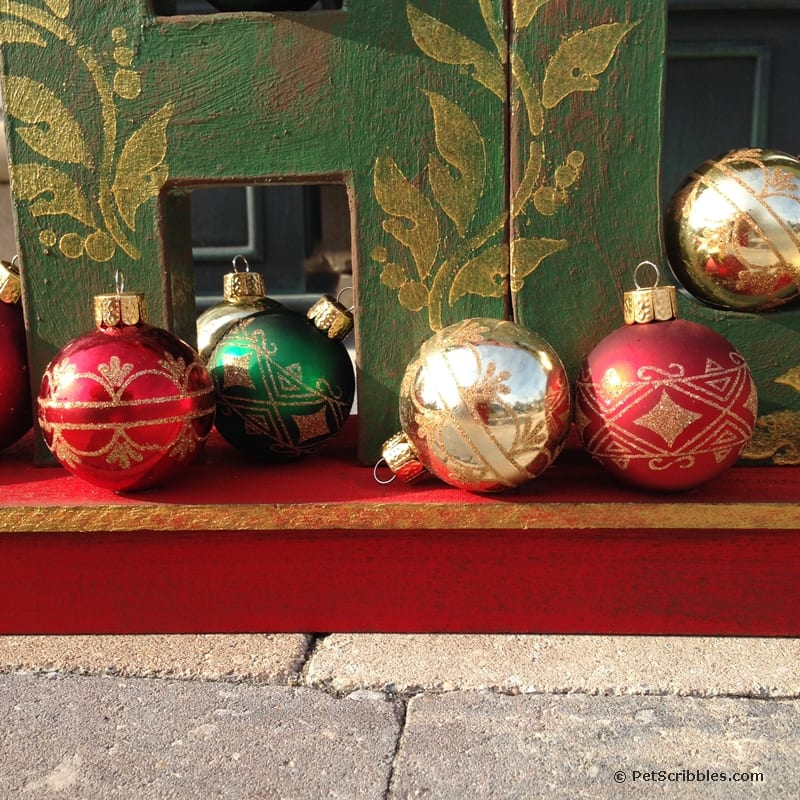Christmas ornaments glued onto painted sled