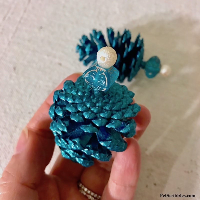 attaching beads to a painted pinecone to make an ornament
