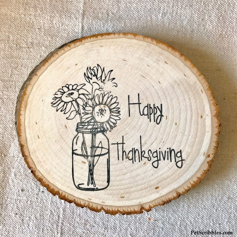 a Happy Thanksgiving stamp design on a wood slice