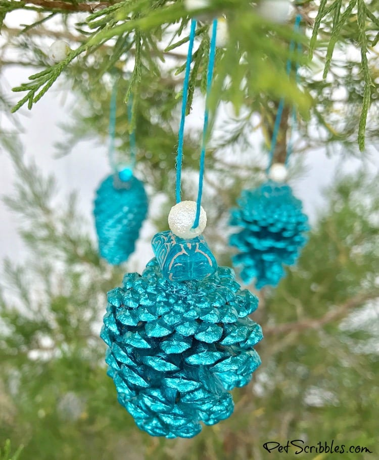 teal pinecone ornaments hanging on a tree