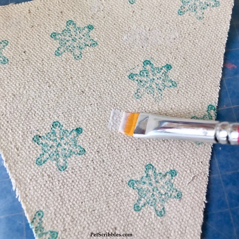 applying sparkle Mod Podge to canvas fabric