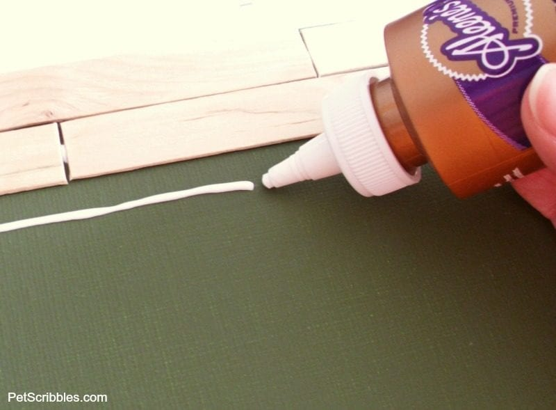attaching craft sticks to canvas with glue