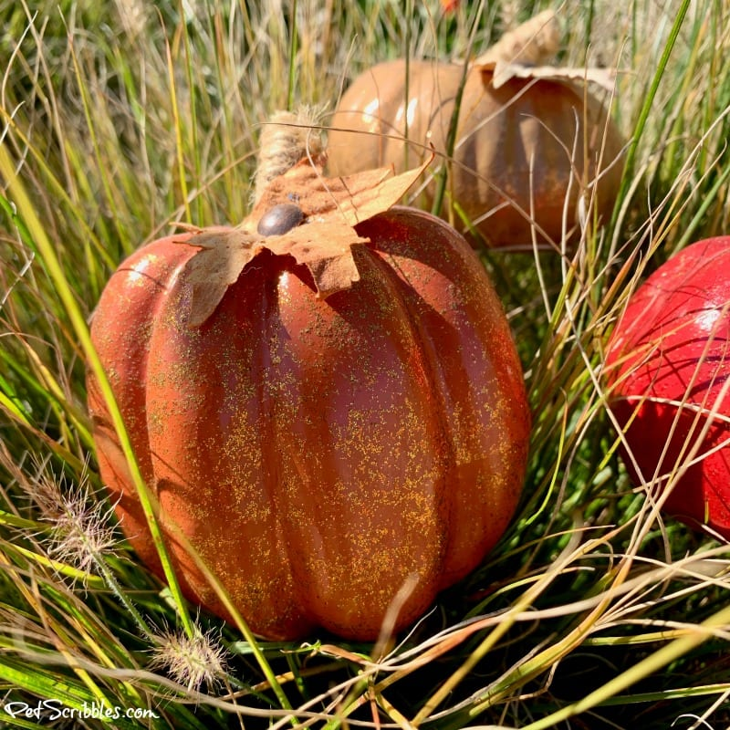 orange glittered pumpkin in ornamental grass