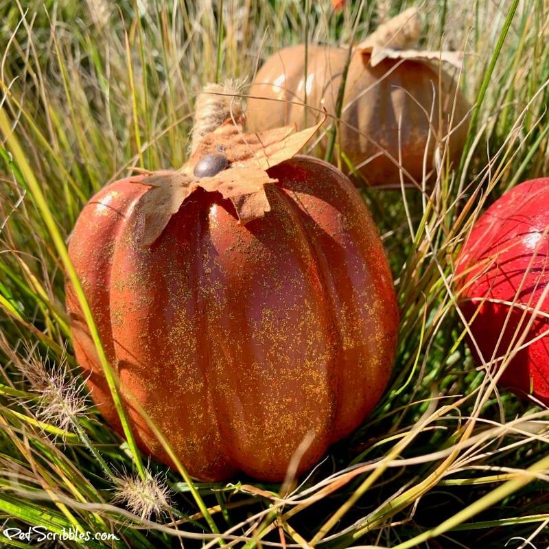 orange glittered pumpkin in ornamental grass