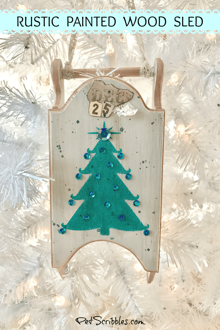 hanging rustic wood sled on white Christmas tree
