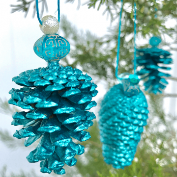 DIY teal pinecone ornaments hanging on evergreen tree outdoors