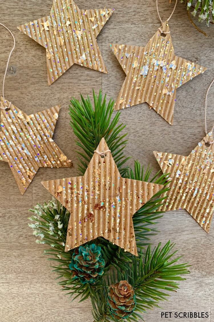 DIY glitter cardboard star ornaments and decorative holiday greenery