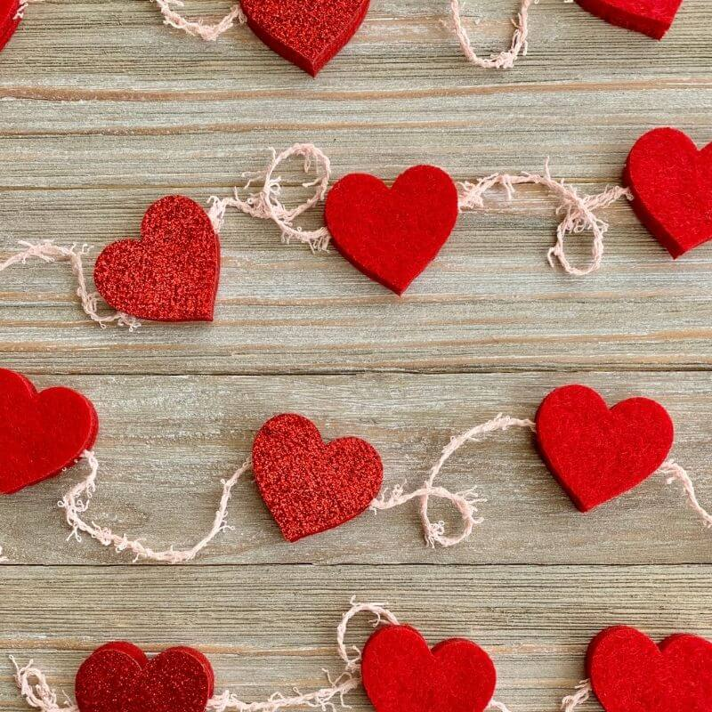 felt heart garland laying on rustic pale wood background